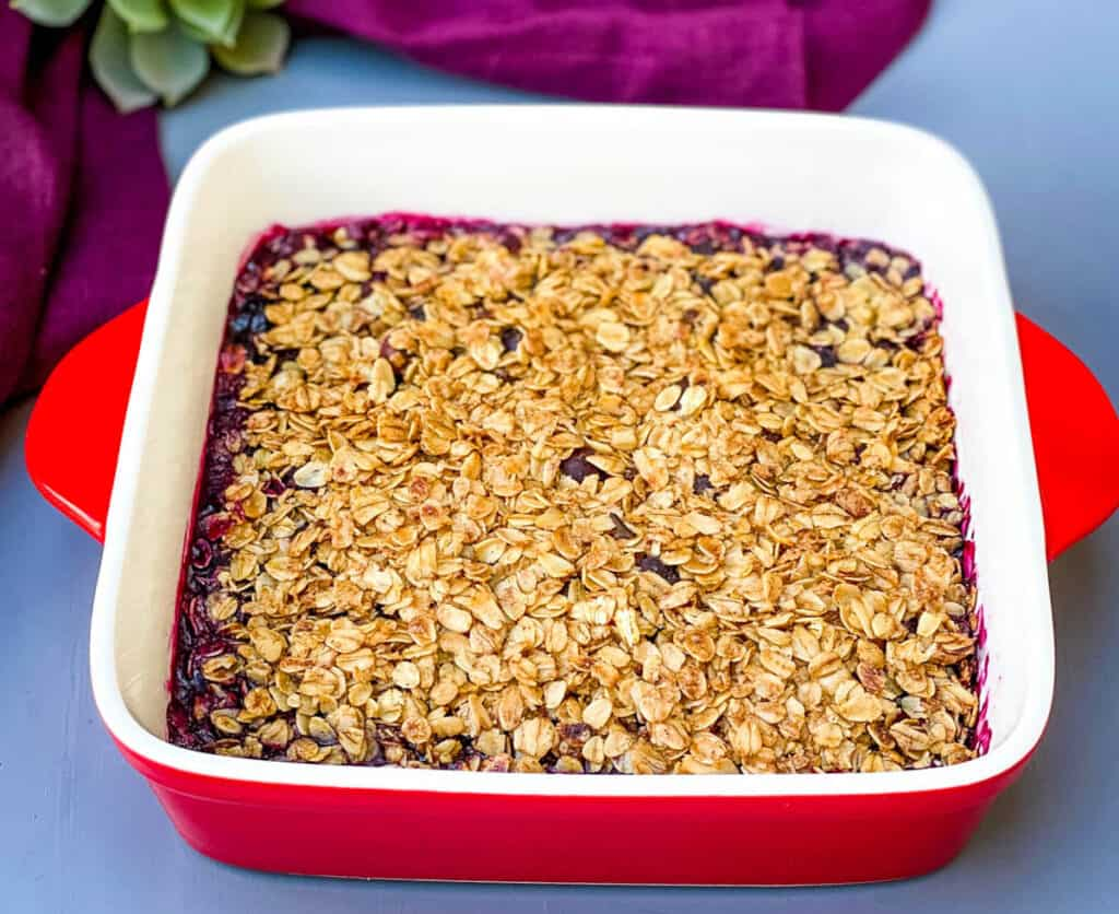 healthy blueberry crisp in a red baking dish