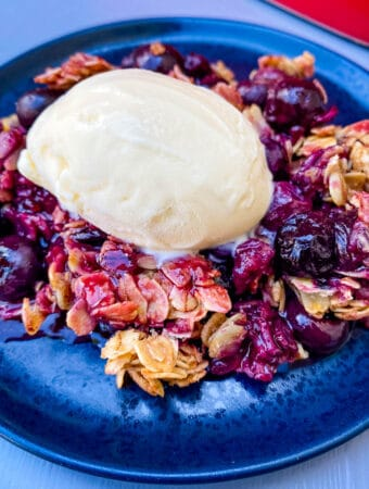 healthy blueberry crisp on a blue plate with a scoop of vanilla ice cream