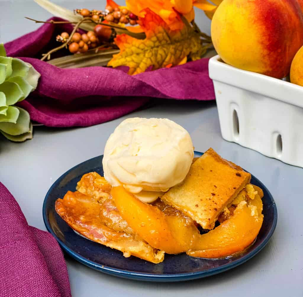 healthy southern peach cobbler on a blue plate with vanilla ice cream