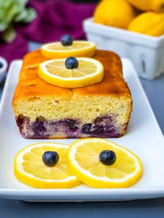 keto low carb lemon blueberry bread on a white plate with fresh lemons and blueberries