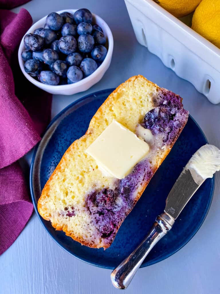 a slice of keto lemon blueberry bread on a blue plate with butter