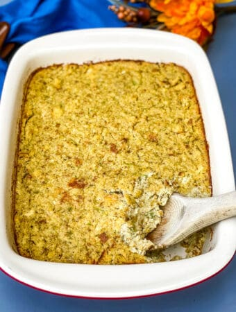 Southern cornbread dressing in a baking dish with a large scoop in a wooden spoon