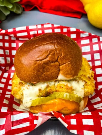 air fryer fish sandwich on a bun with melted cheese and tartar sauce