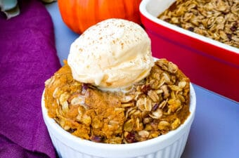 healthy pumpkin crisp in a white bowl with a scoop of vanilla ice cream