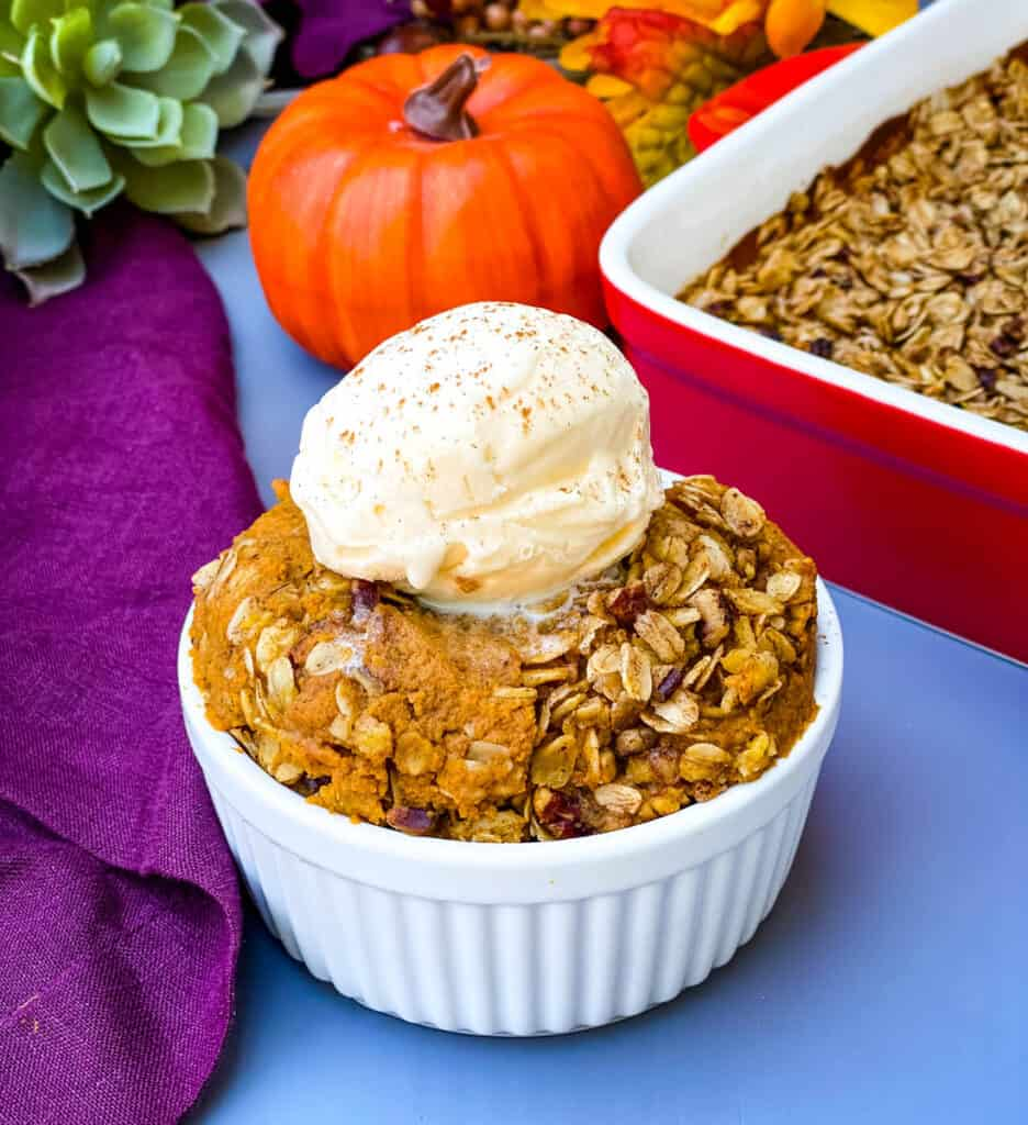 healthy pumpkin crisp in a white bowl with a scoop of vanilla ice cream pinterest image