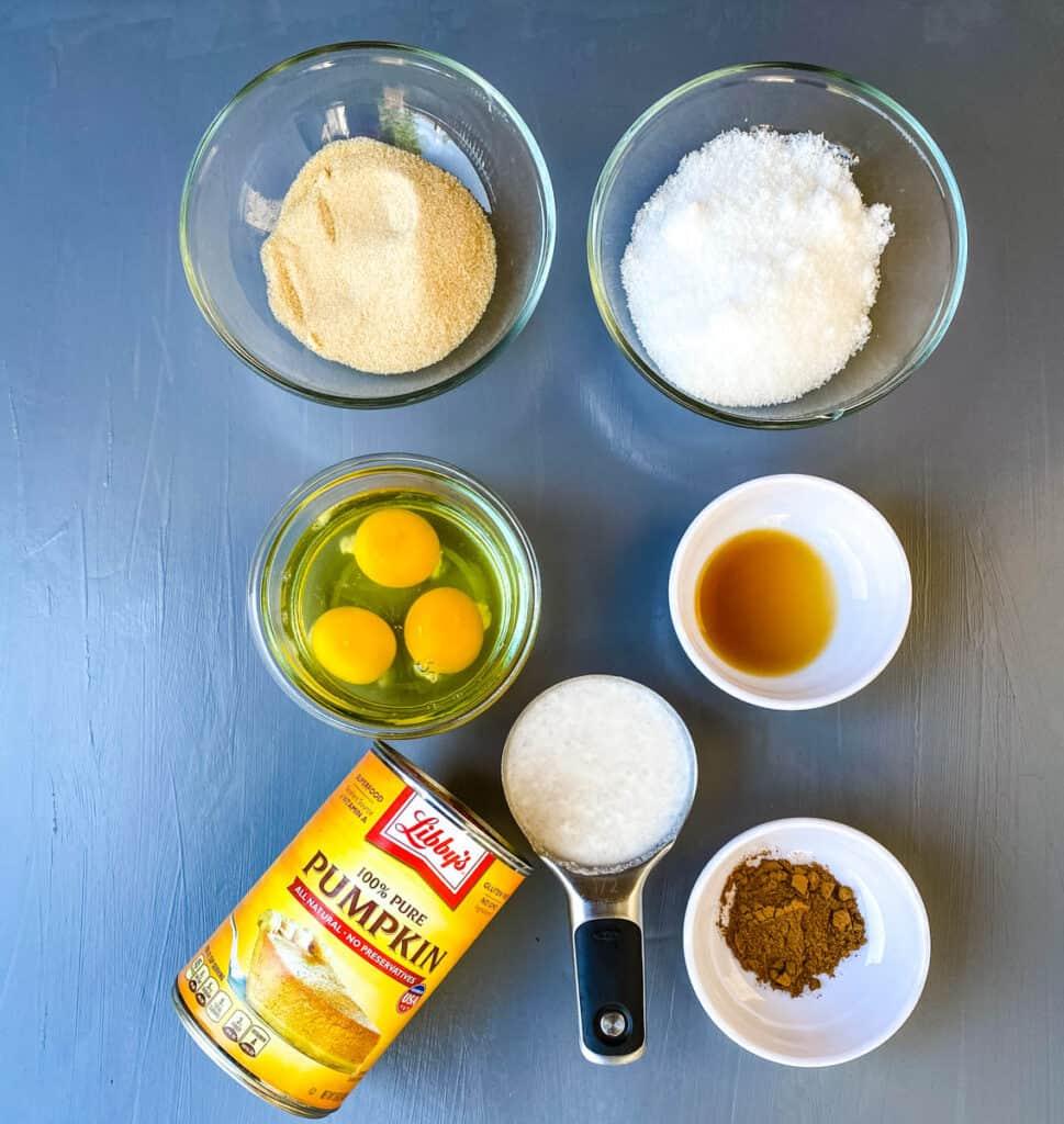 monkfruit sweetener, raw eggs, vanilla, pure pumpkin, pumpkin pie spice, and coconut milk in separate bowls on a flat surface