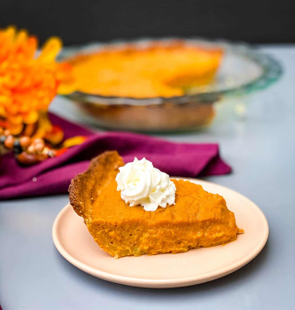 healthy sweet potato pie on a pie plate with whipped cream