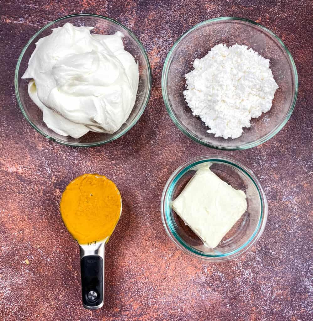cool whip, powdered sweetener, natural peanut butter, and cream cheese in separate glass bowls
