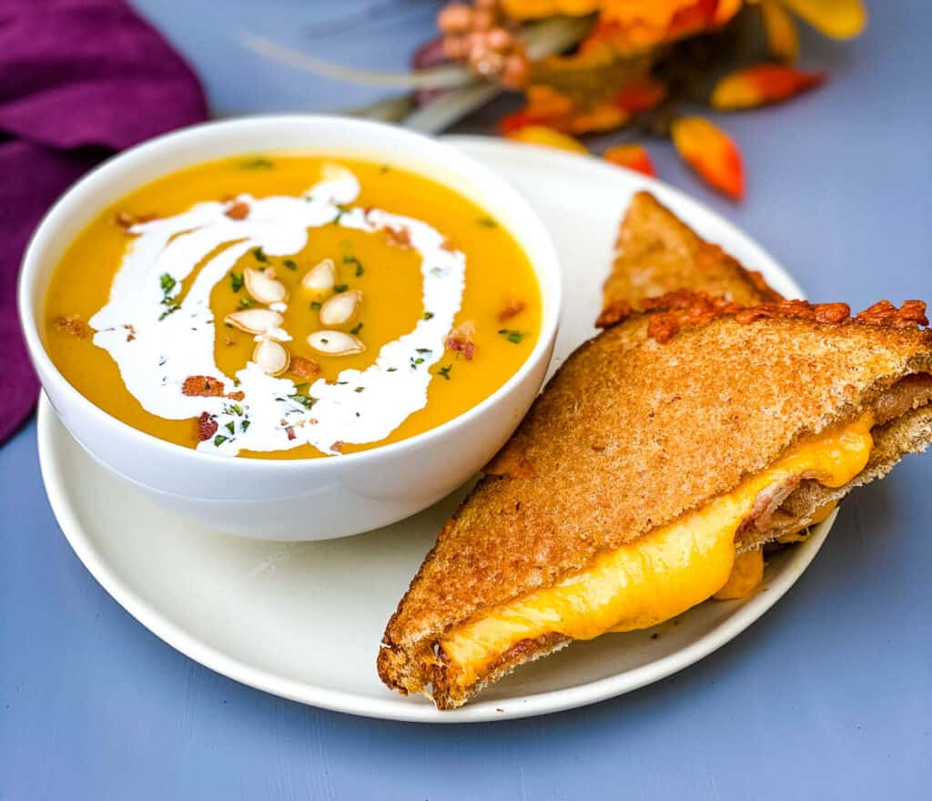 Panera autumn squash soup in a white bowl with a grilled cheese sandwich