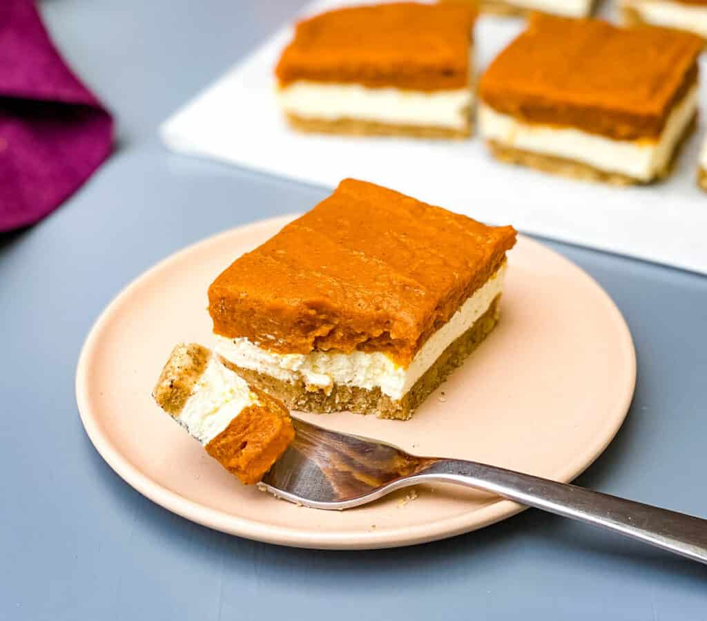 pumpkin cheesecake bars on a pink plate