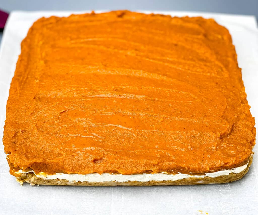pumpkin cheesecake bars on parchment paper