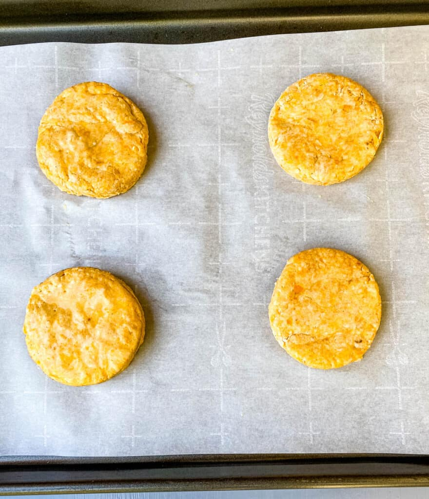 sweet potato biscuits on parchment paper and a sheet pan