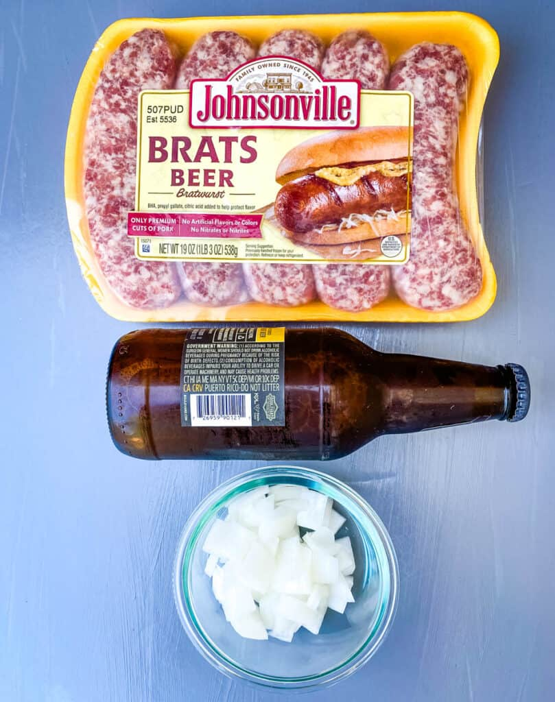 raw uncooked brats, a bottle of beer, and chopped white onions on a flat surface