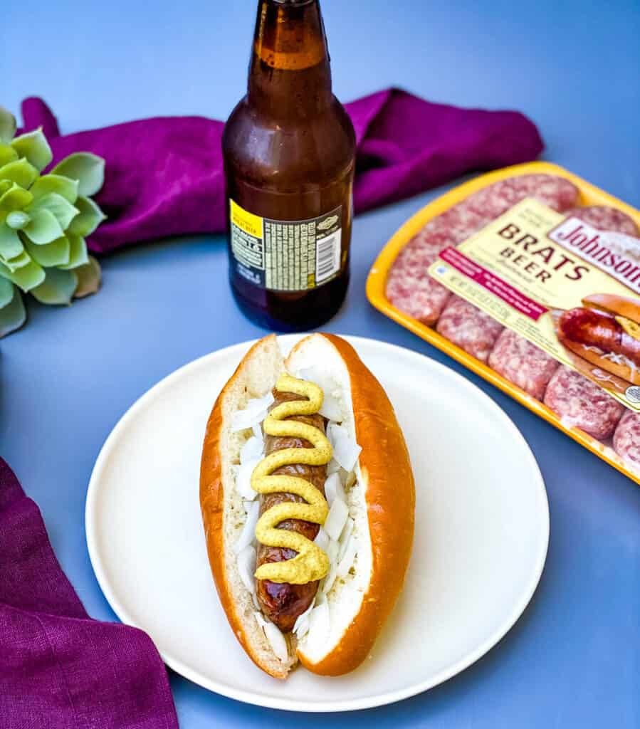 air fryer brats on a plate in a bun with mustard and onions and a bottle of beer