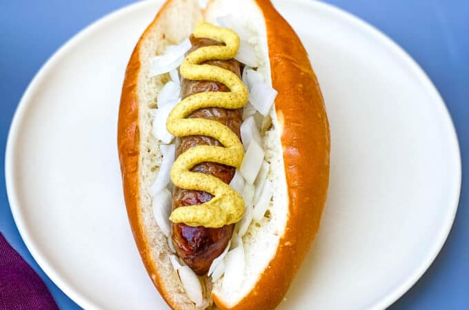 air fryer brats on a hotdog bun with mustard and onions