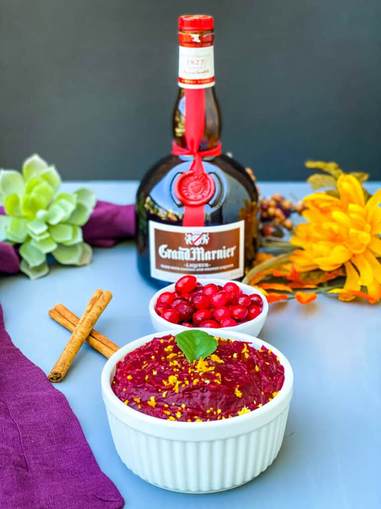 Grand Marnier cranberry sauce in a white bowl with a bottle of Grand Marnier