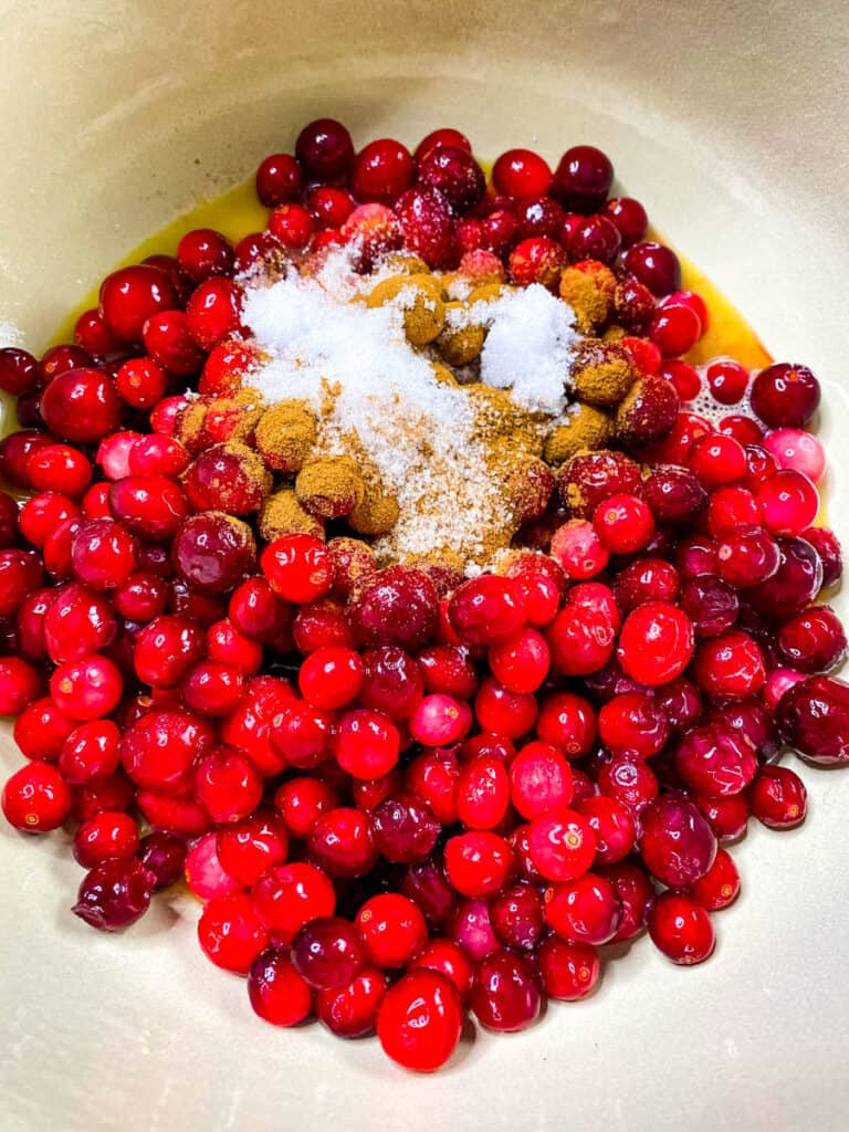 cranberries in a pot with cinnamon, honey, and sweetener