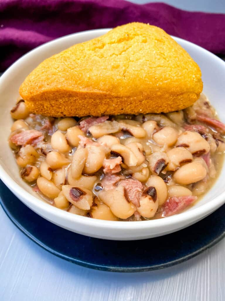 Instant Pot black eyed peas in a white bowl with cornbread