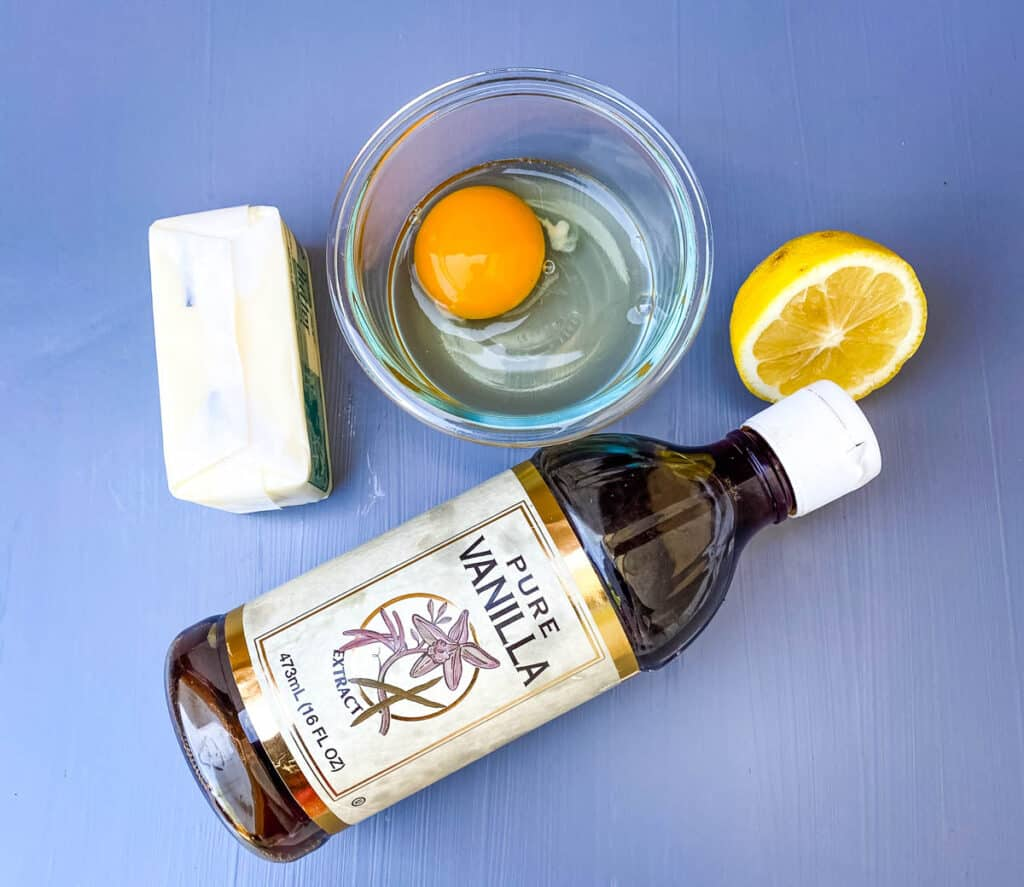 raw egg, fresh lemon, butter, and vanilla extract on a flat surface