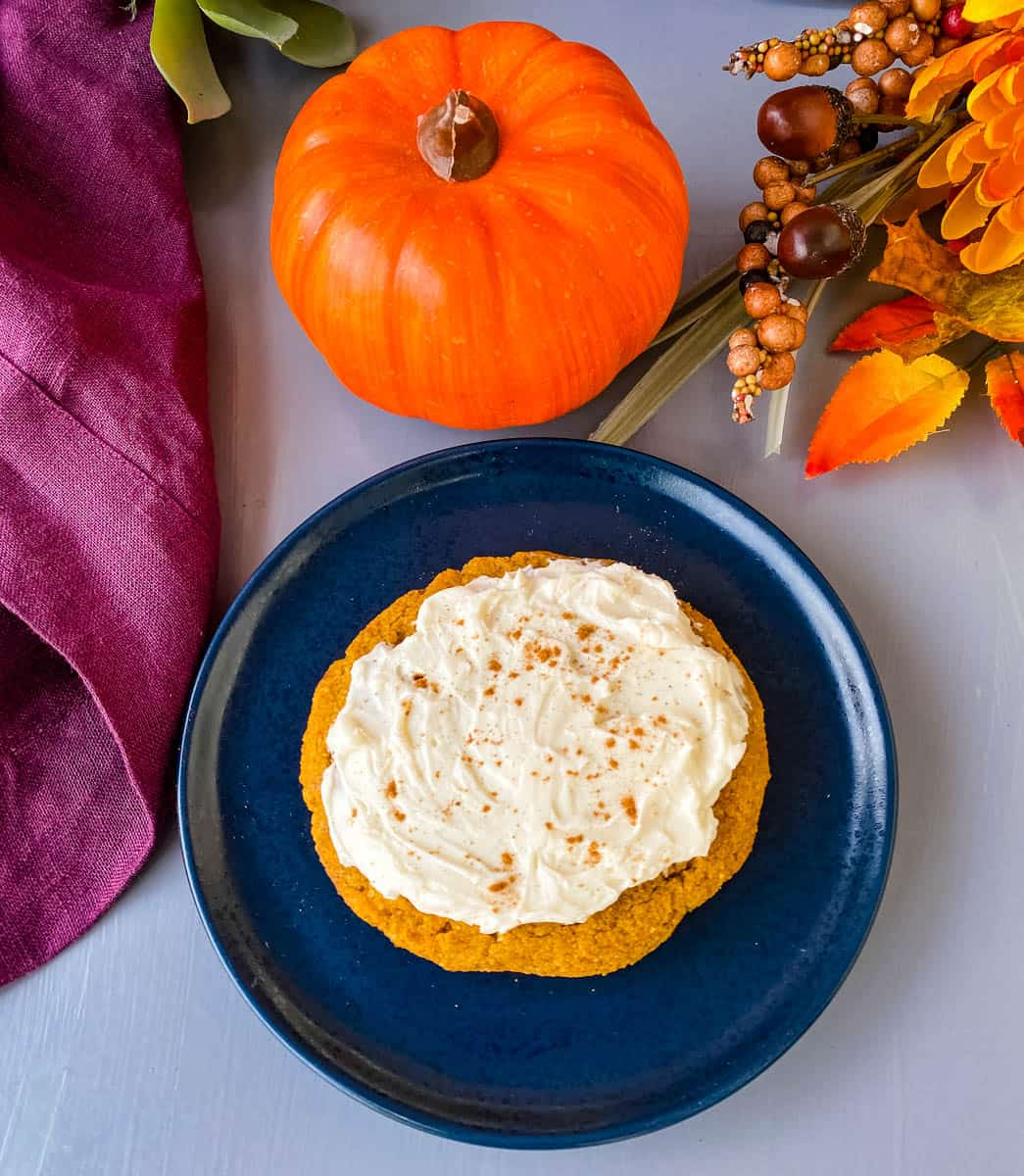 keto pumpkin cookies with cream cheese frosting and cinnamon on a blue plate