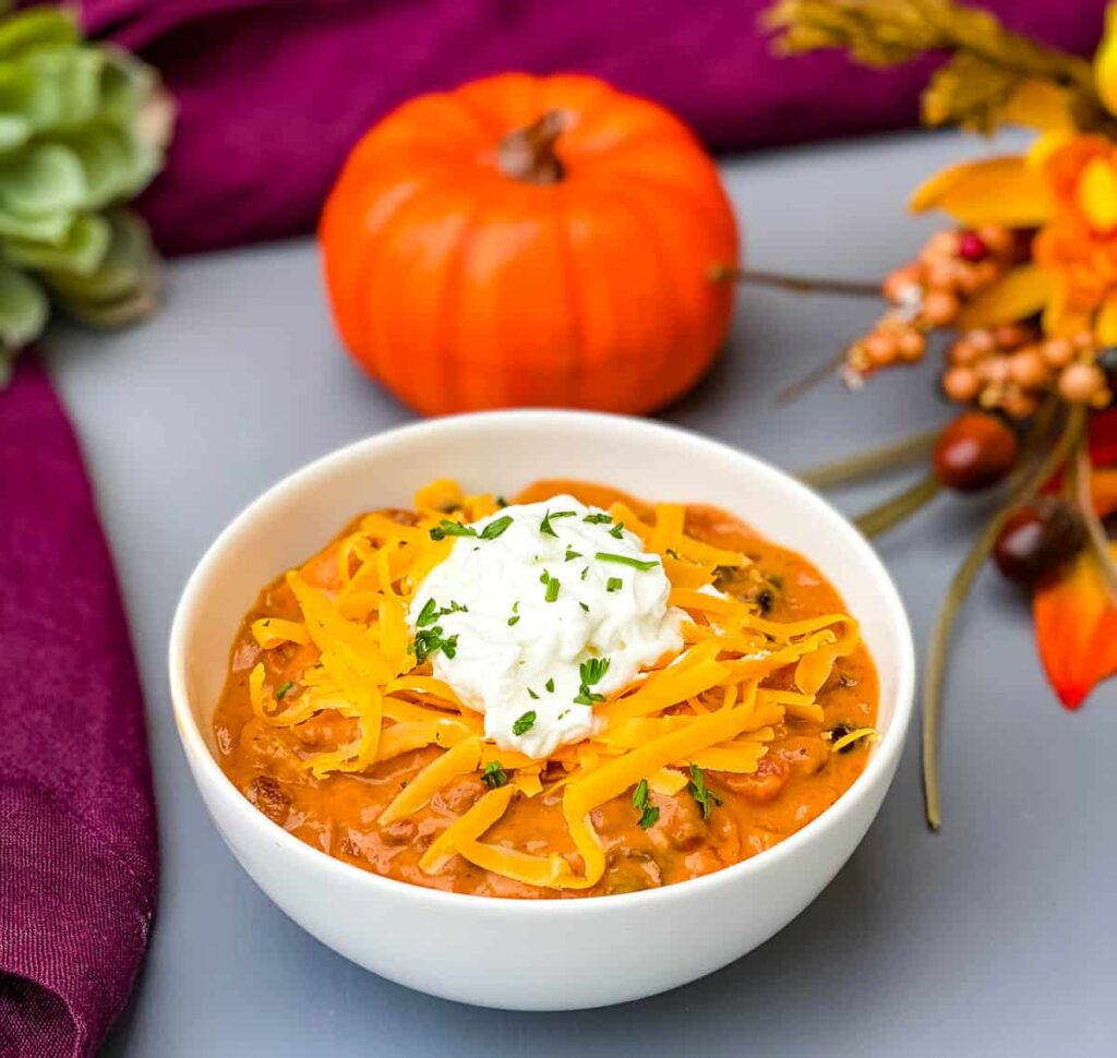 pumpkin chicken chili in a white bowl with a pumpkin and purple napkin in the background