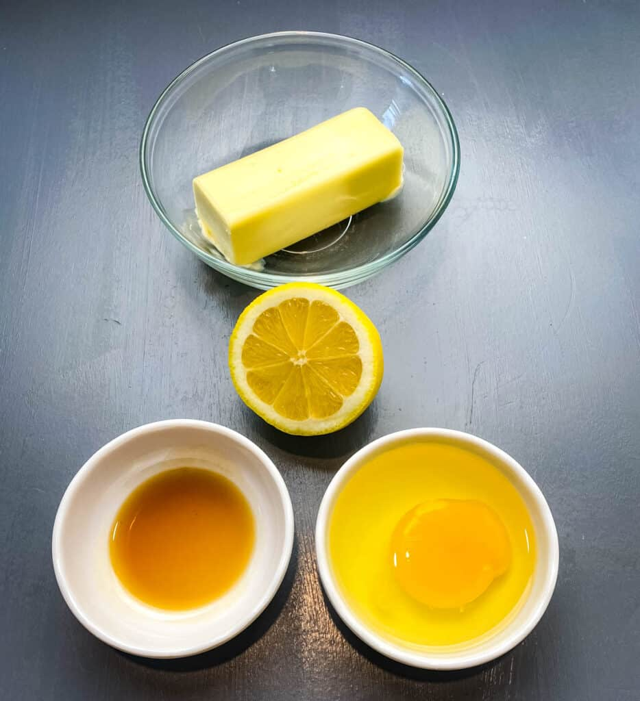 butter, lemon, vanilla, and an egg in glass bowls on a flat surface