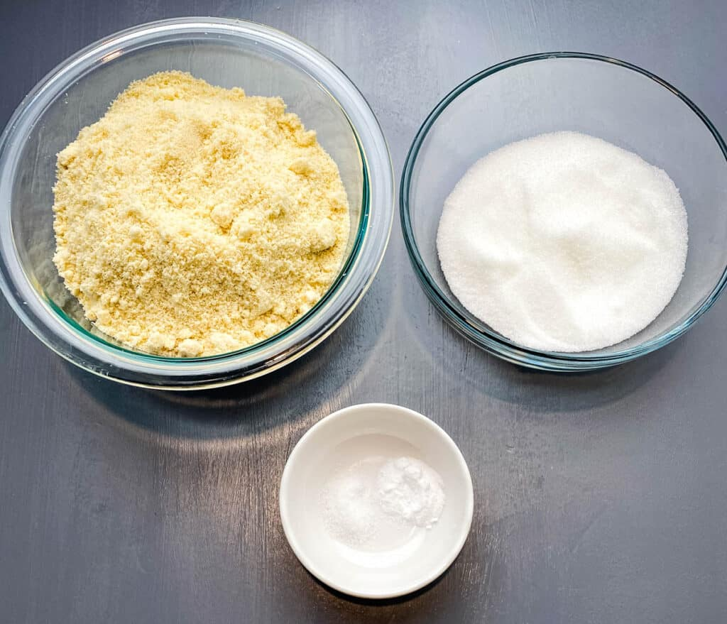 almond flour, sweetener, and baking soda in glass bowls on a flat surface