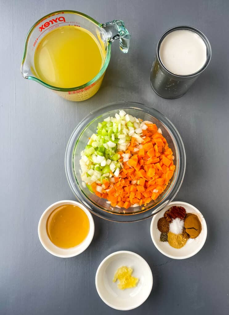 broth, coconut milk, carrots, celery, onions, cinnamon, honey, and garlic in separate bowls on a flat surface