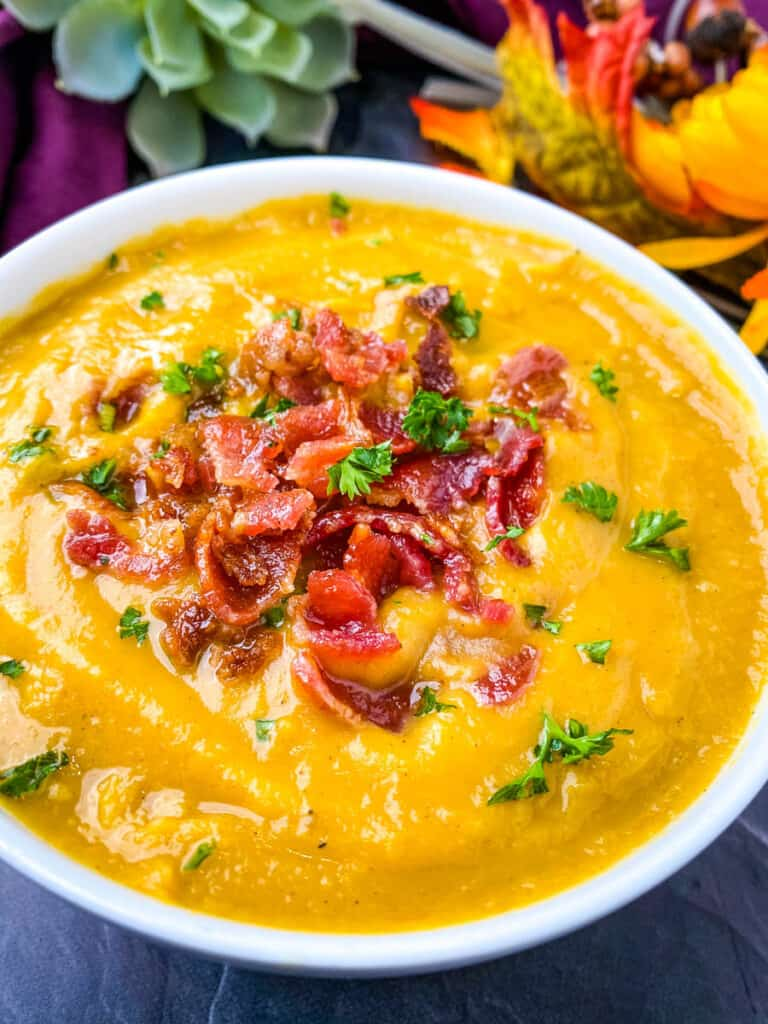 sweet potato soup in a white bowl with chunks of bacon