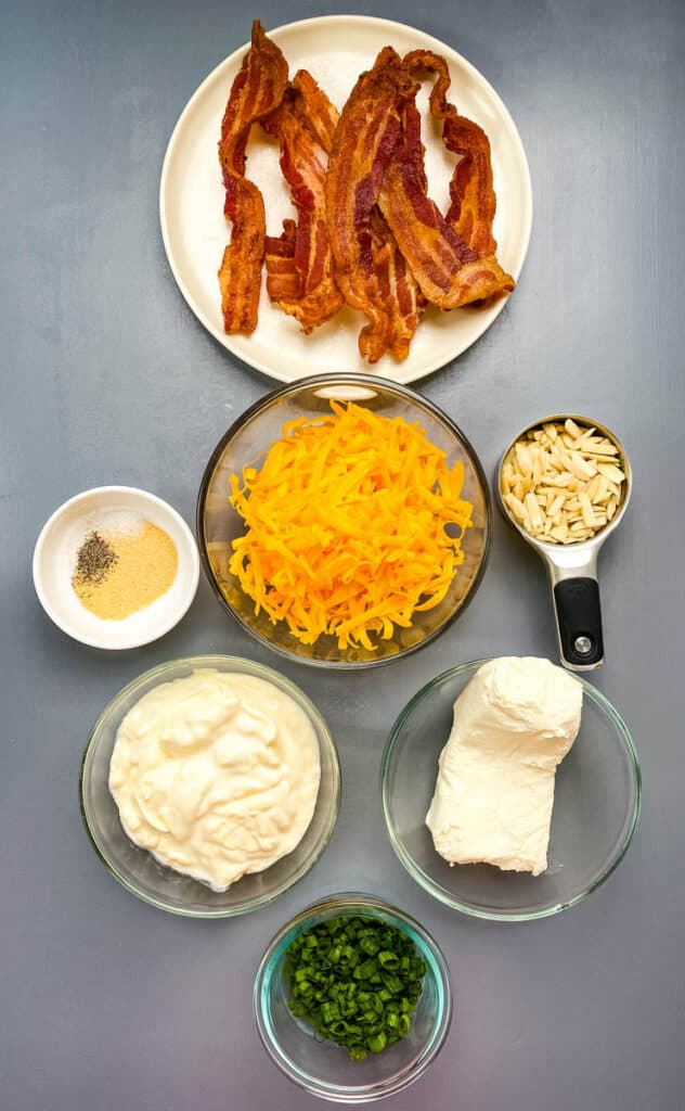 cooked bacon, shredded cheese, cream cheese, mayo, green onions, and slivered almonds in separate bowls on a flat surface