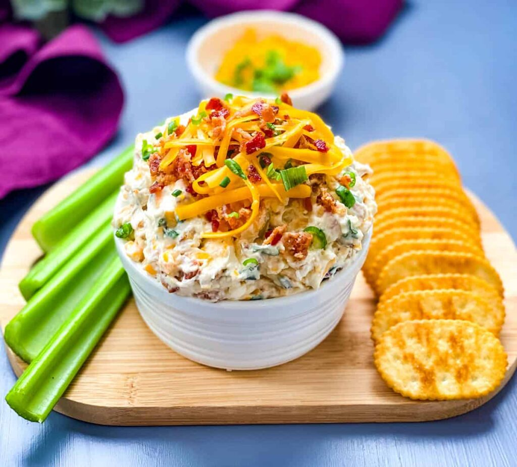 million dollar dip in a white bowl garnished with crackers and celery
