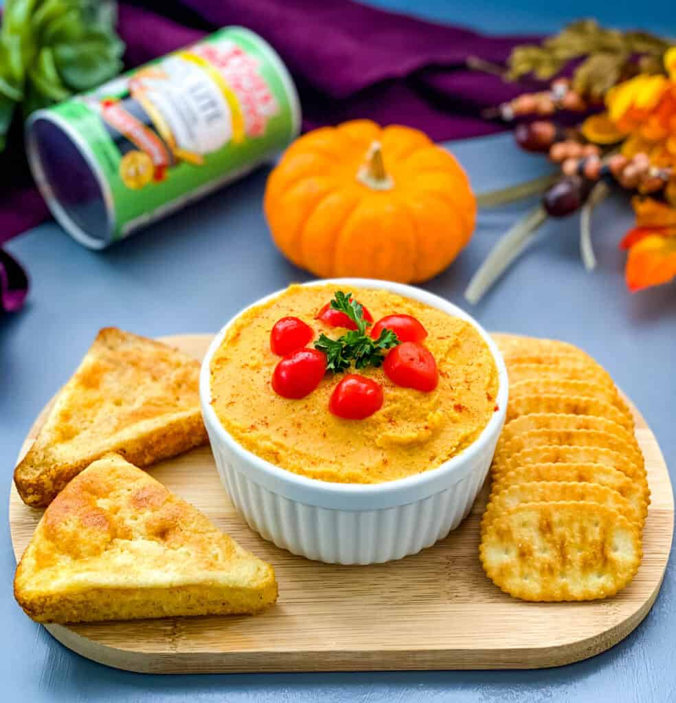 pumpkin hummus on a cutting board with cornbread and crackers
