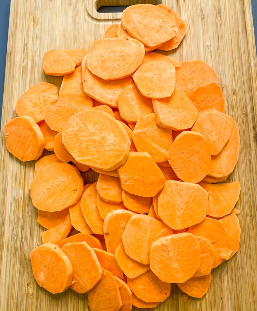 raw and sliced round sweet potatoes on a bamboo cutting board