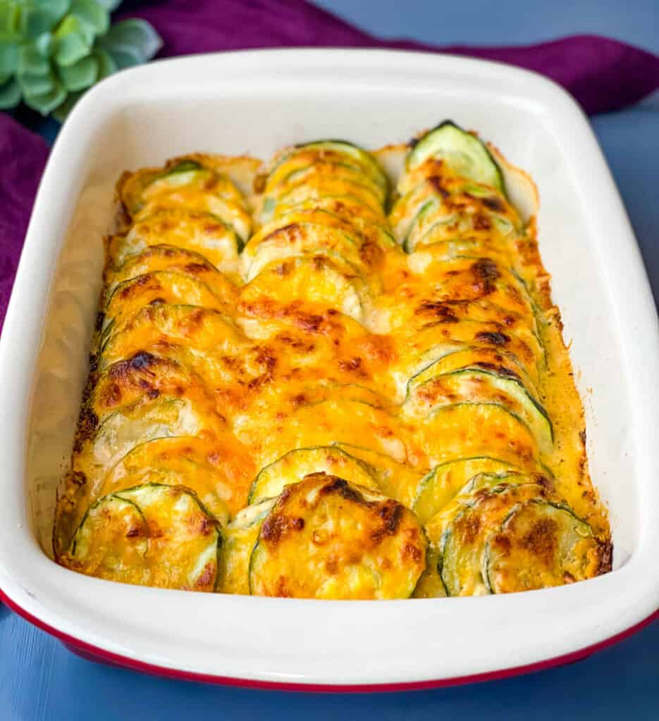 zucchini au gratin scalloped potatoes in a red baking dish