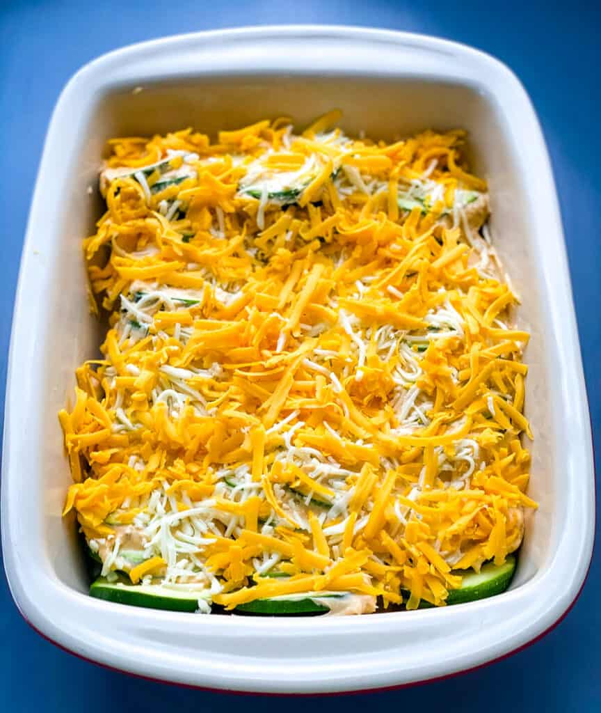 unbaked zucchini au gratin scalloped potatoes in a red baking dish