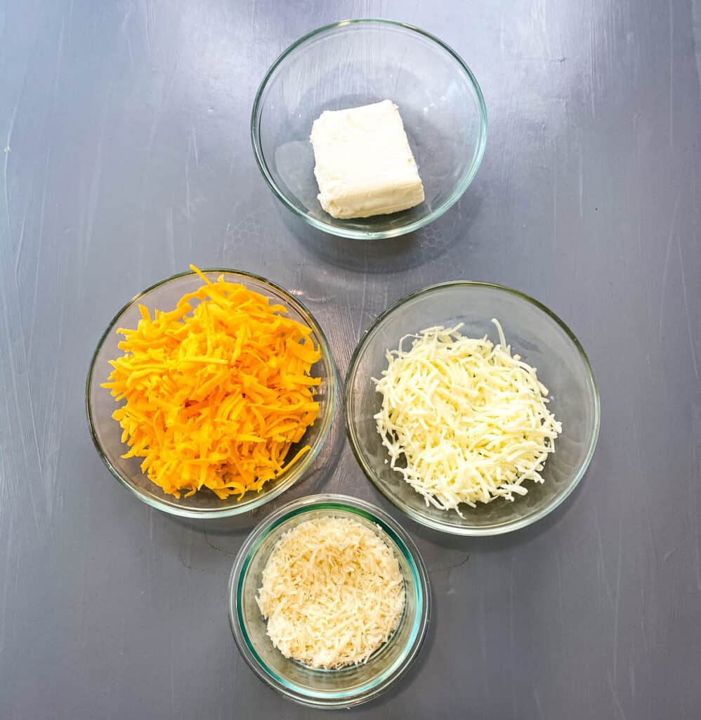 cream cheese, shredded cheddar, mozzarella, and parmesan cheese in separate glass bowls
