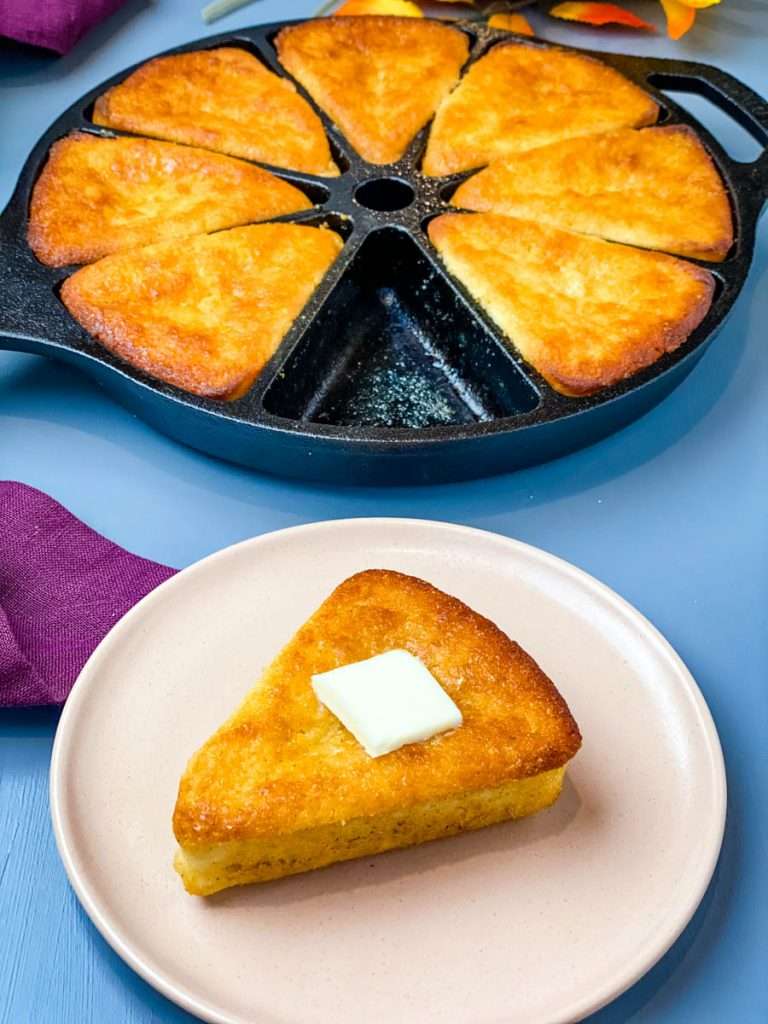 honey cornbread in a cast iron skillet with a slice of cornbread on a plate with butter