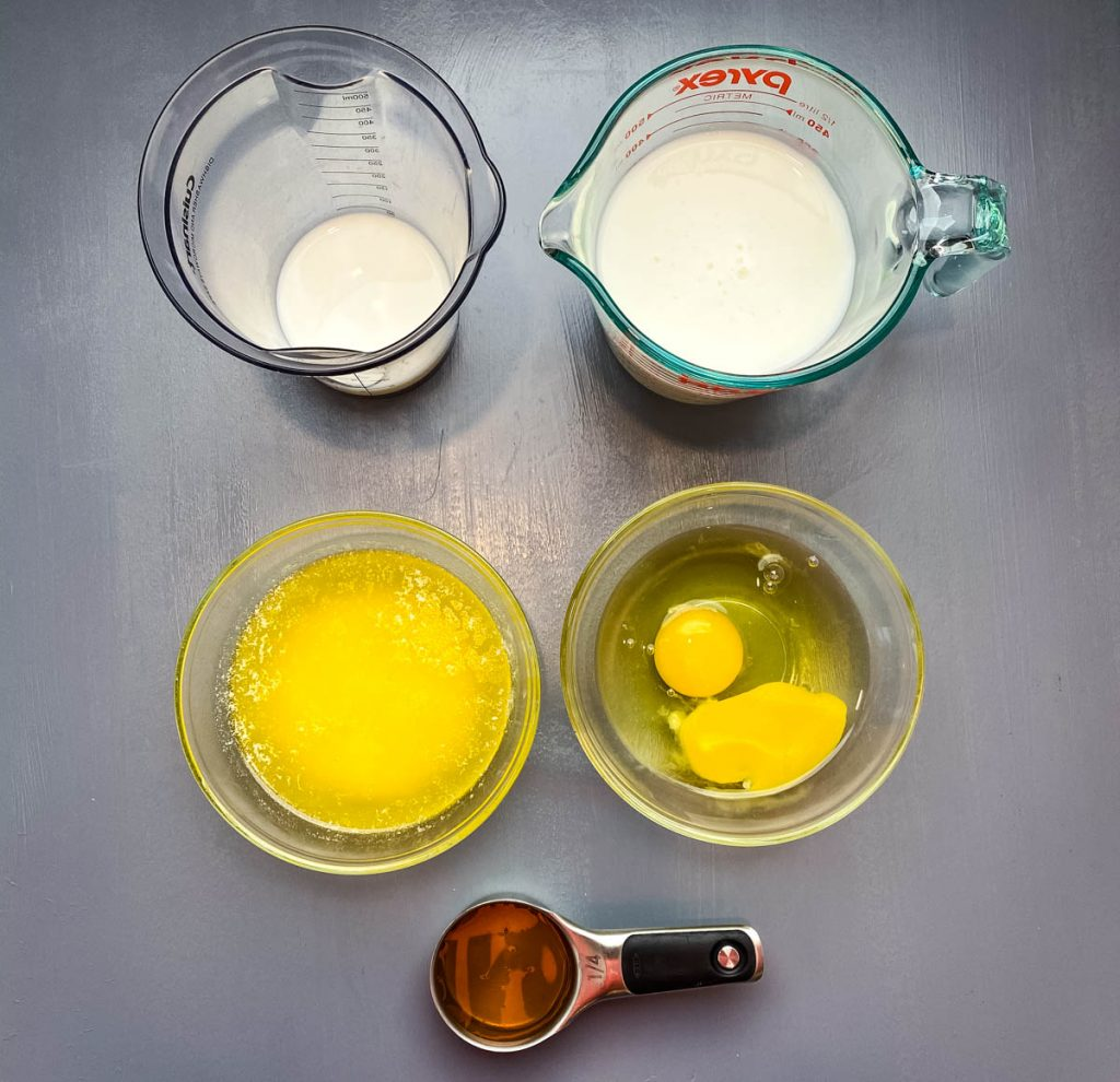 buttermilk, eggs, melted butter, and honey on a flat surface