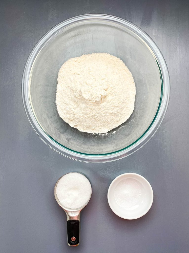 self rising cornmeal, sweetener, and salt in separate bowls on a flat surface