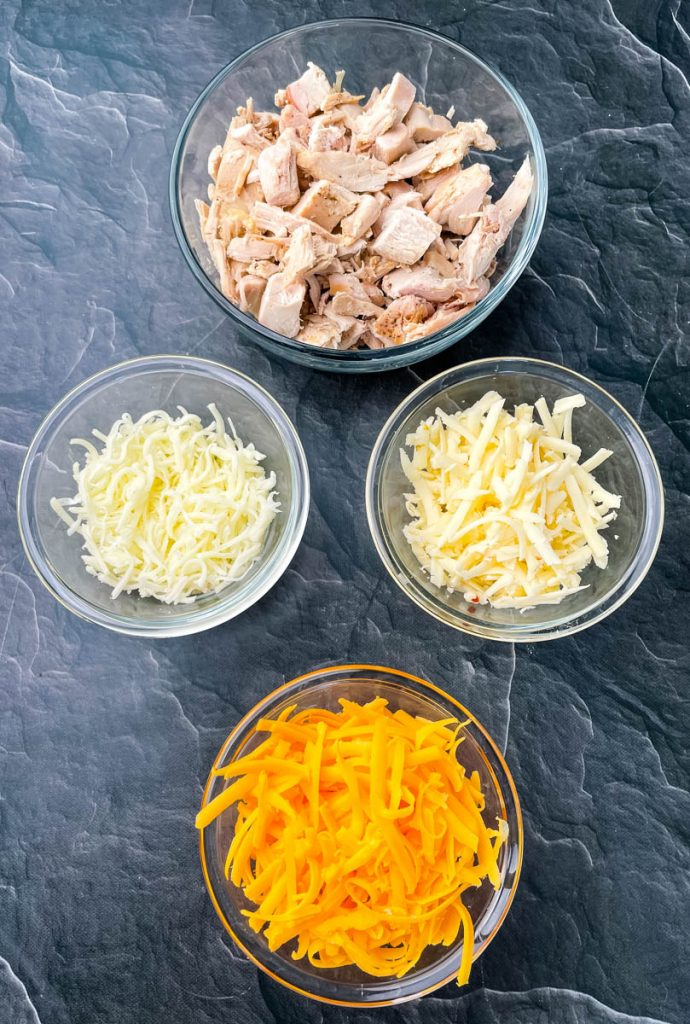 cooked turkey, shredded cheese in glass bowls