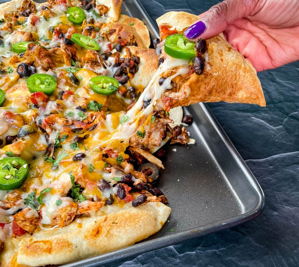 person holding a chip with turkey nachos on a sheet pan