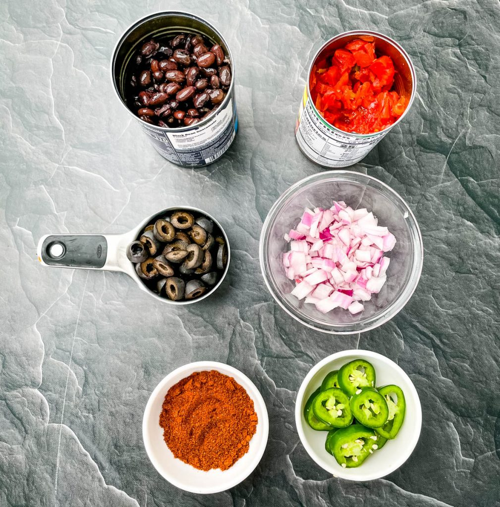 black beans, Rotel, olives, onions, jalapenos, and taco seasoning in separate bowls