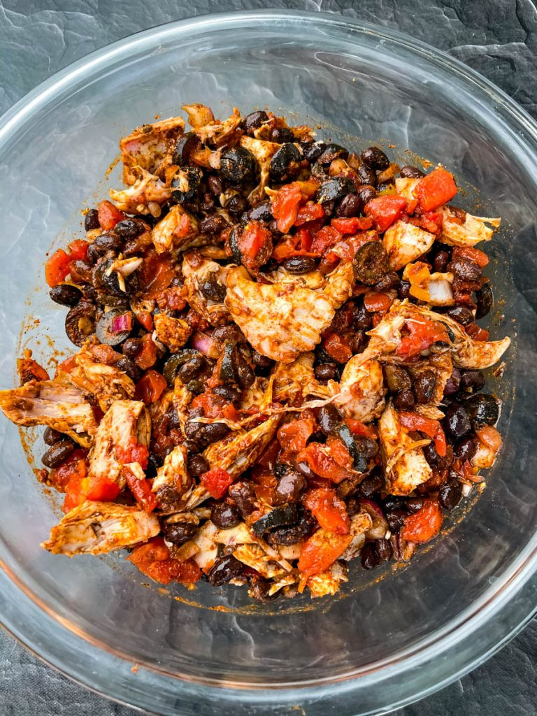 turkey, black beans, onions, Rotel, black olives, and taco seasoning in a glass bowl