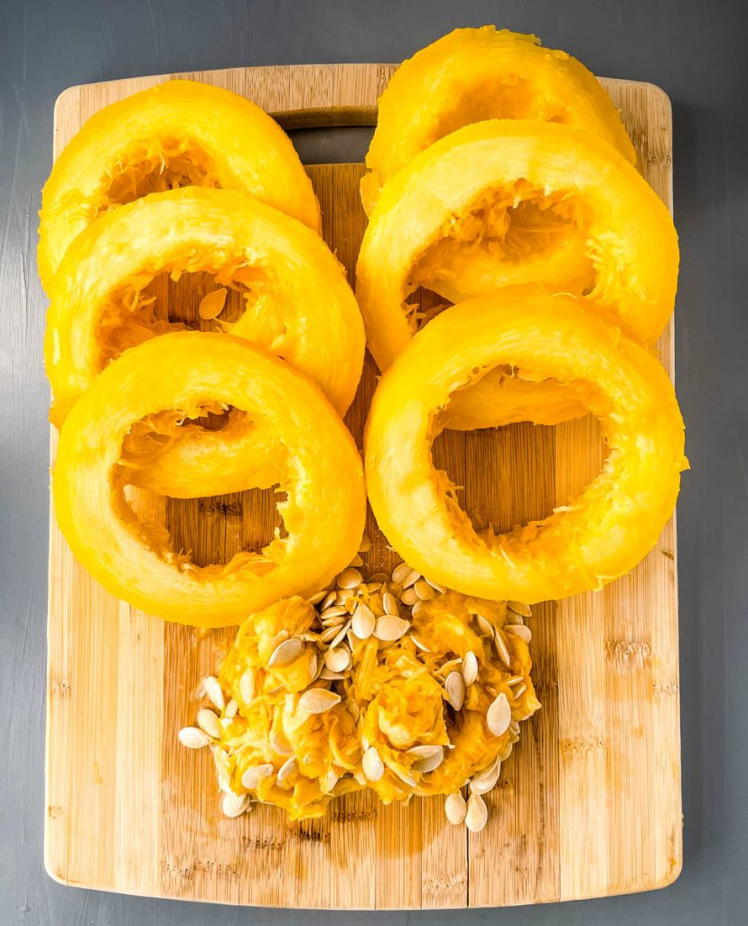 cooked spaghetti squash sliced on a cutting board