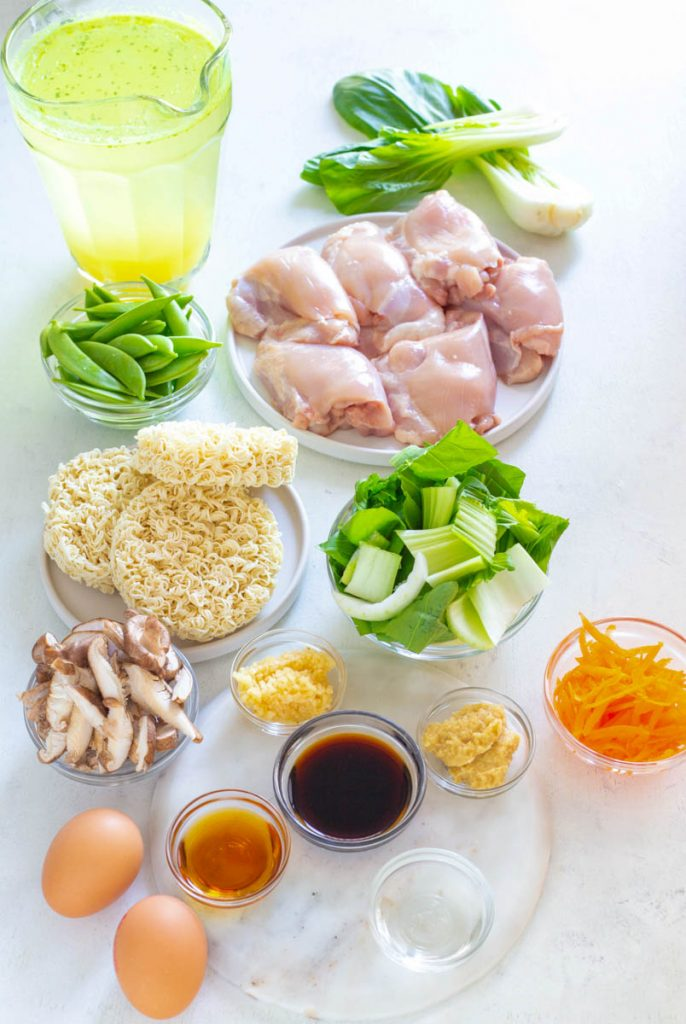 raw chicken thighs, bok choy, eggs, ramen, and vegetables in separate bowls on a counter