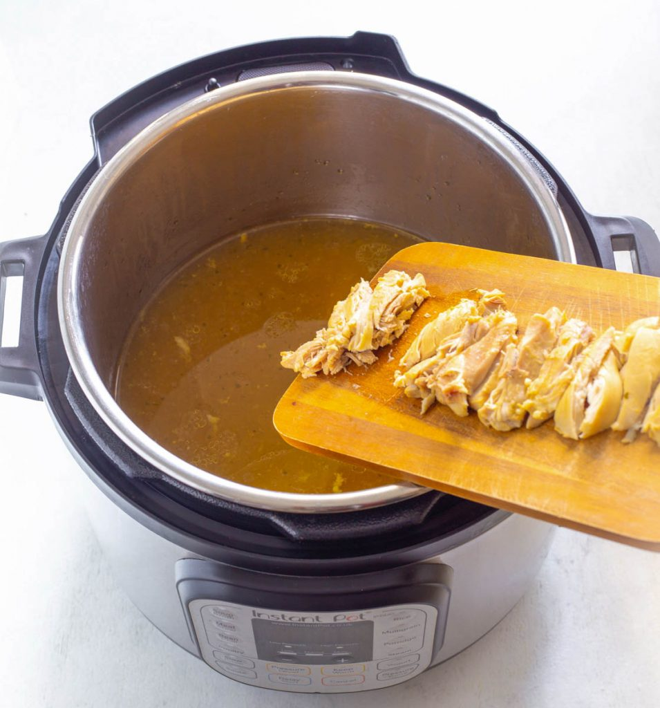 sliced chicken thighs in broth in an Instant Pot