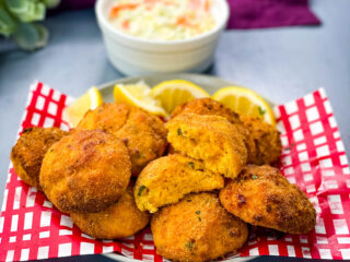 air fryer hushpuppies on a plate with fried fish and coleslaw