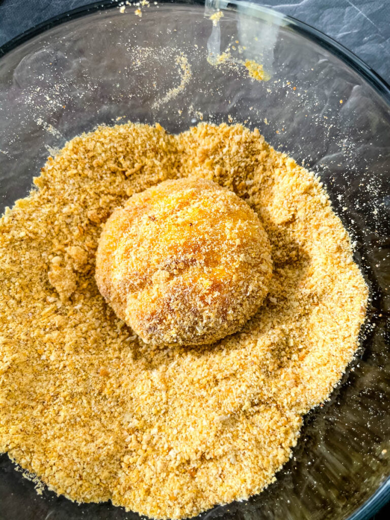a hushpuppy dredged in breadcrumbs in a glass bowl