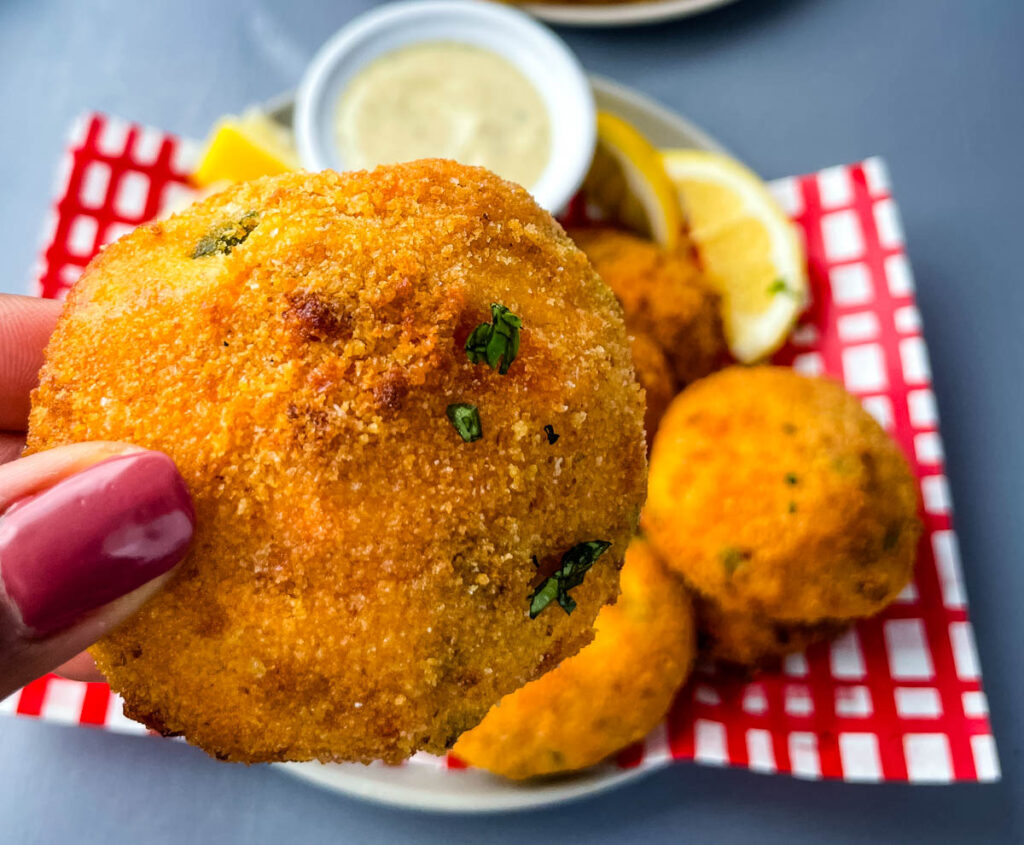 person holding an air fryer hush puppy