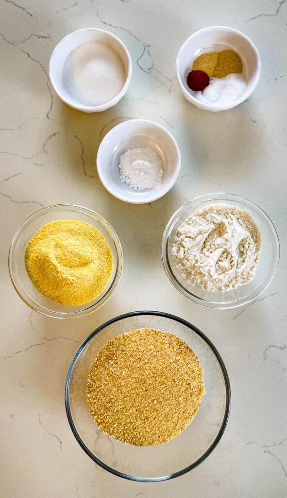 cornmeal, flour, baking powder, seasonings, and sweetener in separate bowls on a flat surface